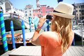 Woman in Venice taking picture of Rialto bridge