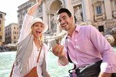 Couple of tourists throwing coins in Trevi fountain water
