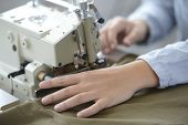 Closeup on dressmaker hand using sewing machine