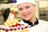 stock photo of confectioners  - Portrait of young confectioner holding cake - JPG