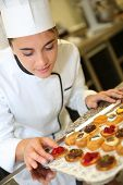 Cheerful pastry cook holding tray of pastries