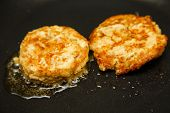 stock photo of patty-cake  - Two crab cakes frying in a saute pan in hot oil