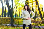Cute woman wearing a beige sweater in autumn park
