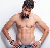 waist up portrait of a young topless man standing with his hands on his hips and looking at the came