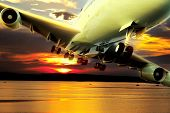 Passenger plane over lake at sunset