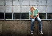 Sad teen girl sitting on a concrete parapet. Real people series