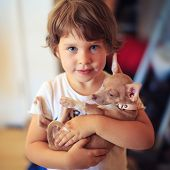 stock photo of baby dog  - Portrait of toddler girl with baby dog pet - JPG