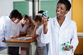 Young female teacher looking at molecular structure with students in background