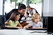 Glückliche Lehrerin Schüler im Umgang mit Computer in der Schule zu unterstützen