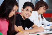 Portrait of happy teenage schoolboy sitting with female friends at desk in classroom