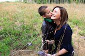 Cute boy kissing mother's cheek in sunny field