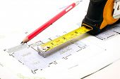 measuring tape and a pencil over a construction blueprint of a house