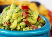 Closeup of a bowl of fresh guacamole with corn tortilla chips. Intentional shallow depth of field.