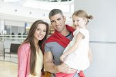 Father and mother pose with young daughter in shopping mall