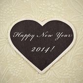 happy new year 2014 written in a heart-shaped blackboard on a vintage background, with a retro effec