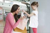 Madre dando regalo de la hija de bolso de compras de papel