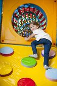 Young girl climbing up ramp into tunnel at soft play center