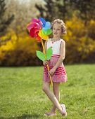 image of wind wheel  - Young girl holding large Flower shaped wind wheel - JPG