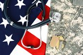 Military fatigues and dog tags on an American Flag with a stethoscope to illustrate health care in t