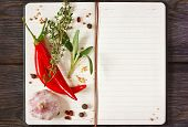 image of mustard seeds  - Open recipe book with chili and spices on a wooden background - JPG