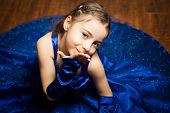 Young girl in blue dress sending a kiss