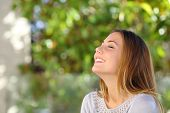 stock photo of breathing exercise  - Young happy smiling woman doing deep breath exercises outdoor with a green background - JPG