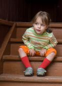 little girl sits on stairs and curiously looks toward