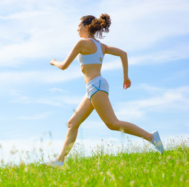 stock photo of athletic woman  - Mature woman athlete practicing in a spring meadow from a complete series - JPG