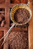 hot chocolate flakes  in old rustic style silver sieve on wooden spicy box, shallow dof