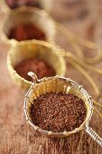 hot chocolate flakes with chilli flavor in old rustic style silver sieve, shallow dof