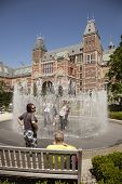 Tourists Cooling Themselves In Fountain Behind Rijksmuseum Amst