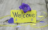 Welcome place card on wood table with purple flowers and hearts