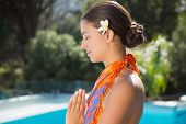 Brunette in sarong meditating by the pool outside at the spa