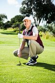 stock photo of kneeling  - Golfer kneeling holding his golf club on a sunny day at the golf course - JPG