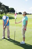 Lady golfer holding eighteenth hole flag for partner putting ball on a sunny day at the golf course