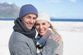 Attractive couple smiling at camera on the beach in warm clothing on a bright but cool day
