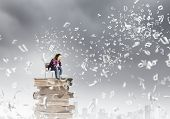 Young girl sitting on high pile of books
