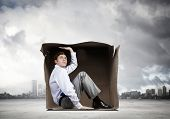 Young frustrated businessman sitting in small carton box