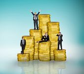Composite image of business people on pile of coins against blue vignette