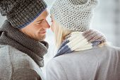 Couple in warm clothing facing each other on a cold day in the city