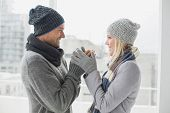 Cute couple in warm clothing smiling at each other on a chilly day