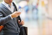 stock photo of conversation  - Handsome young man in shopping mall using mobile phone - JPG