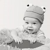 picture of baby frog  - cute baby playing in the hat frog lying on his stomach on a white background  - JPG
