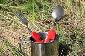 tourist spoon, fork in cup on grass background