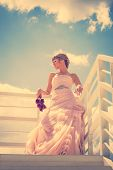 blonde bride in elegant wedding-dress hold flower bouquet lean on fence outdoor summer day