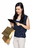 Woman with shopping bag and touch on tablet