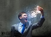 Angry businessman screaming furiously in to mobile phone