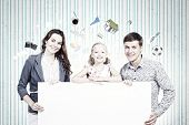 Young happy family with white blank banner. Place for text