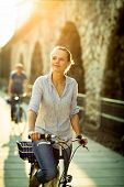 Pretty, young woman riding a bicycle in a city with her boyfriend (color toned image; shallow DOF)