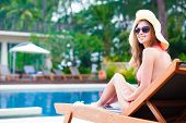 Happy young woman in bikini enjoying her time on chaise-longue luxury pool side